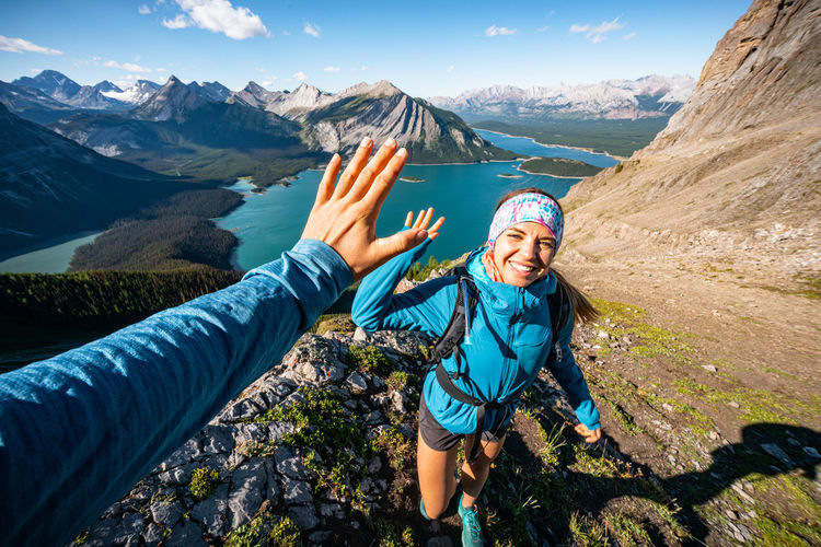 Woman with arms outstretched against mountain range