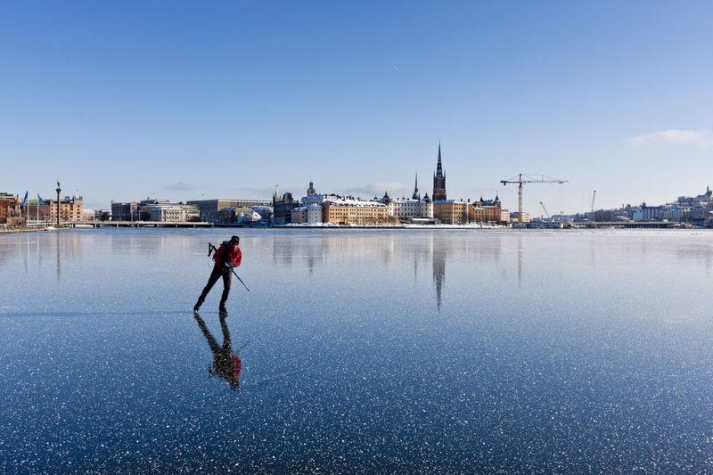 Full length of man standing on snow covered city against sky