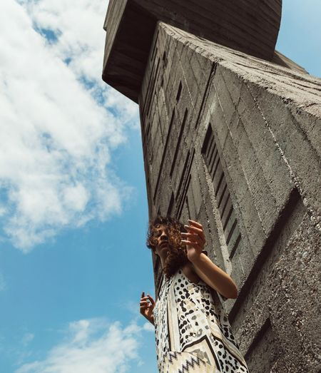 Low angle view of woman standing by concrete wall against sky