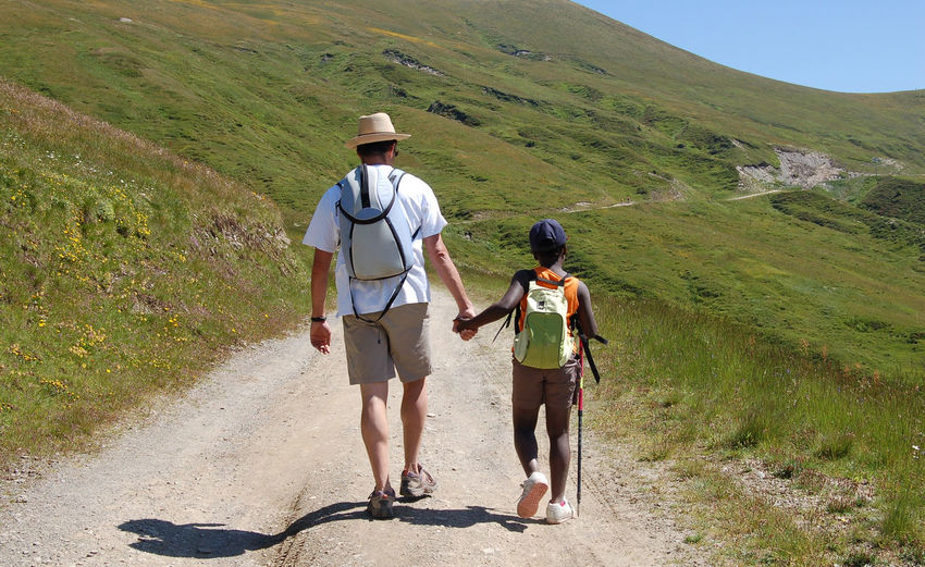 Full length of father and son walking on mountain road