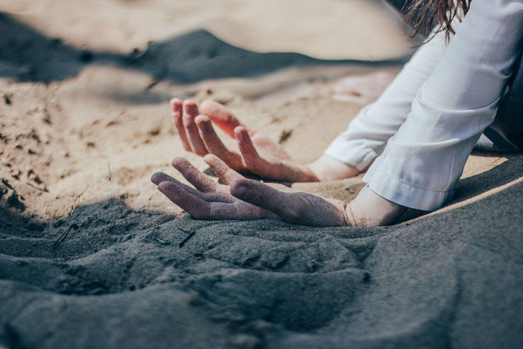 Low section of woman sitting on sand at beach