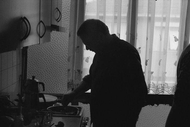 Man Standing In Kitchen At Home