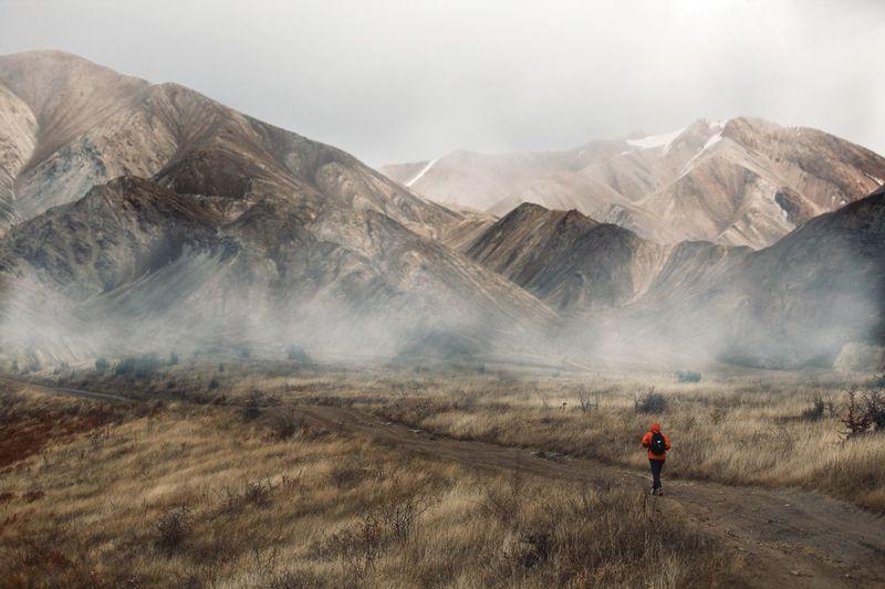 Rear view of man walking by mountain range against sky