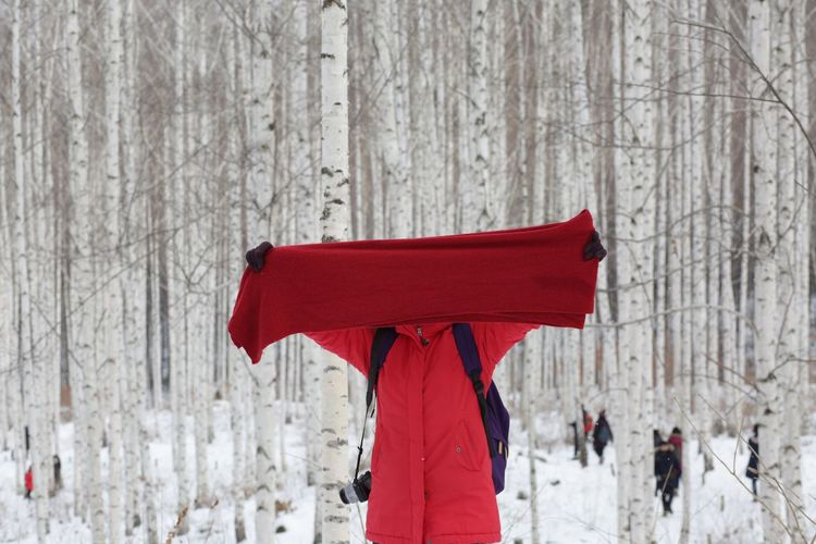 Woman with covered face and arms raised standing in forest during winter