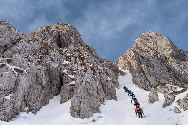 Low angle view of people climbing snow covered mountain