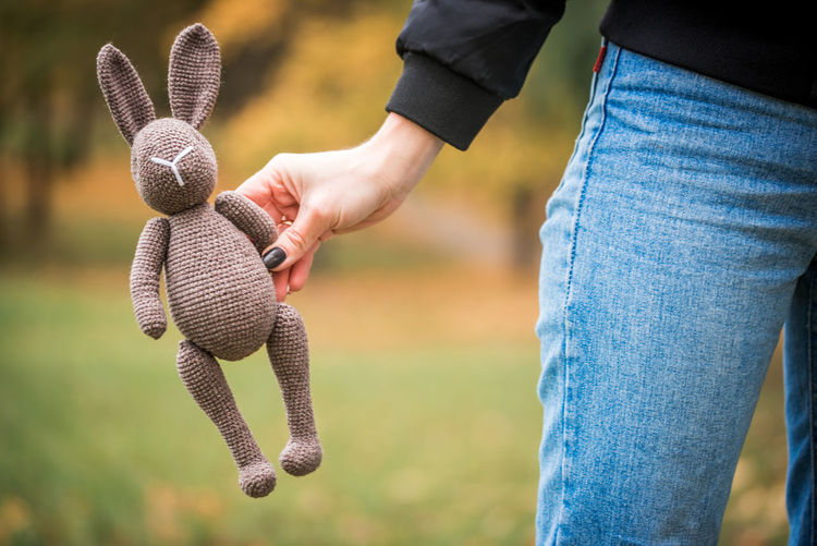 Midsection of woman holding stuffed toy outdoors