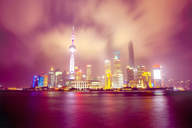 Illuminated Cityscape In Front Of Huangpu River Against Cloudy Sky