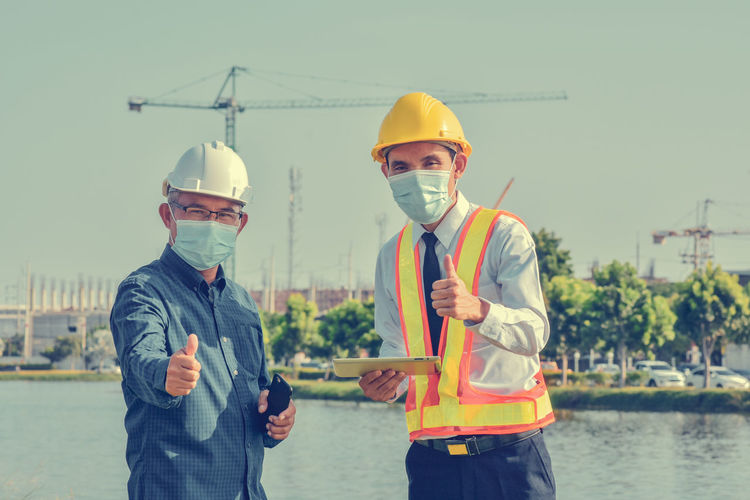 Young man with umbrella standing at construction site