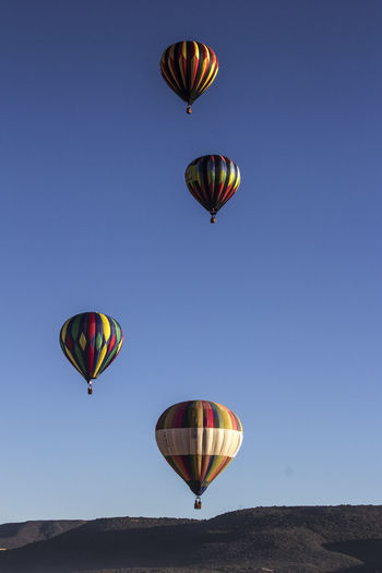 Colorful hot air balloons flying over mountain against clear blue sky
