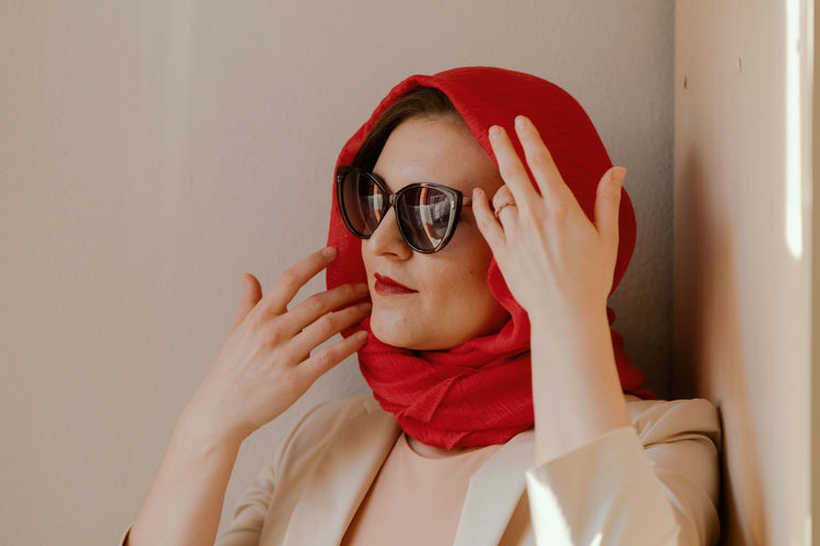Portrait of young woman wearing sunglasses against wall
