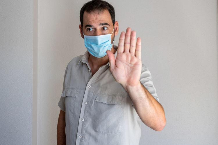 Man wearing flu mask gesturing while looking away at home