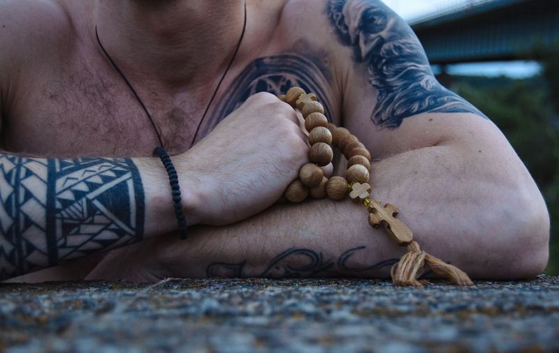 Midsection Of Man With Tattoos On Body Holding Rosary Beads