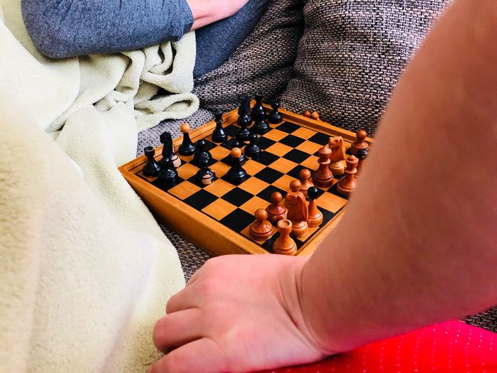 Cropped hands playing chess at home