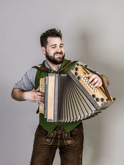 Musician Costume Leather Trousers Tradition Traditional Austria Green Pose Accordion Man Young Shorts Friendly Proud Happy Play Music Fun Joy Single One Background Copy Space Studio Entertainment Mountains Shirt STAND Hobby Leisure Cool Studio Shot One Person Three Quarter Length Standing Indoors  Front View Gray Background Mid Adult Smiling Young Adult Holding Adult Beard Looking Away Gray Mid Adult Men Portrait Young Men