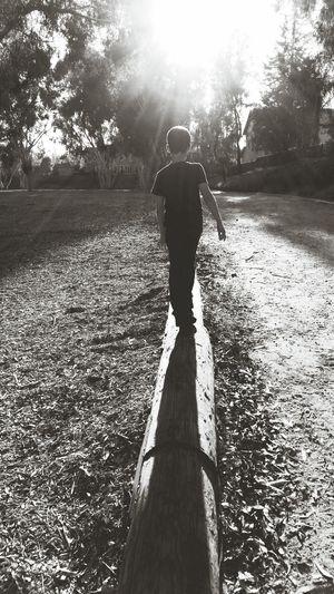 Boy Walking On Log Balancing Black And White Photography Park Life Peaceful Sun Shining Silhouette Shadow