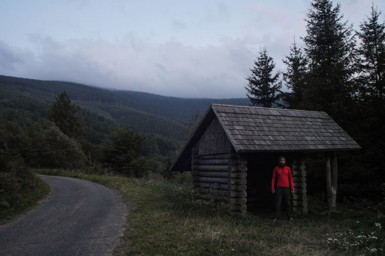 simple wooden cabin used as a hiking shelter with hiker standing inside, czech republic Backpacking Camping Chalet Czech Republic Hiking Lavvu M Nature Standing Trekking Adventure Architecture Beauty In Nature Cabin Cloud - Sky Czechia Eruope Forest Grass Hiker Ladnscape Land Log Mountain Mountains Nature One Person Outdoors People person Plant Real People Rear View Refuge Shelter Sky Standing Tree Wooden