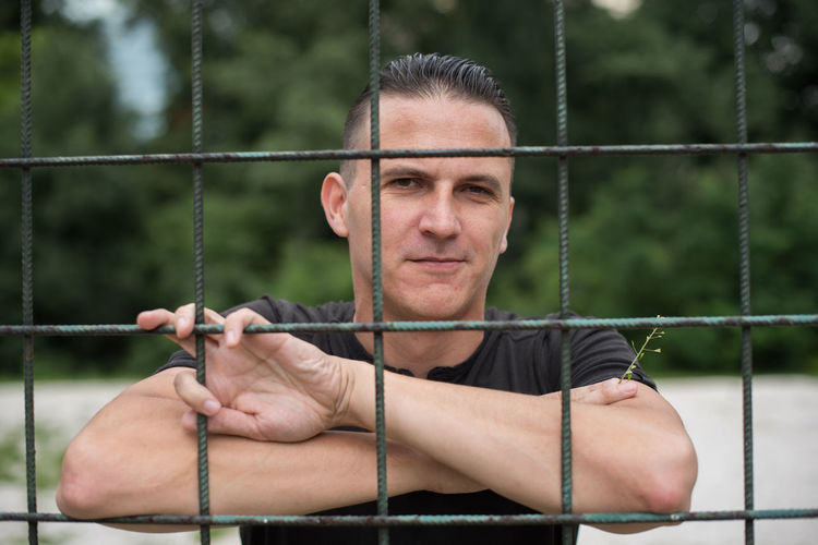 Portrait Of Man Holding Metal Fence Against Trees