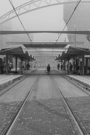 Railroad station platform in city against sky