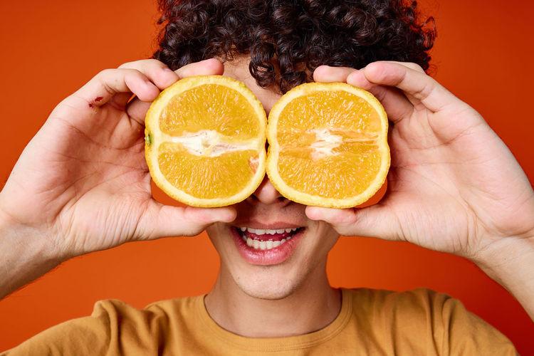 Close-up portrait of woman holding apple against orange background