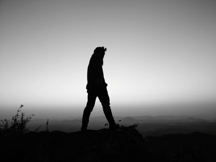 Silhouette man standing on rock against clear sky