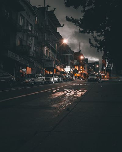 Cars On Street By Buildings In City At Night