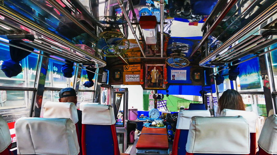 a local bus in thailand City Life Old Bus Travel Photography Adult Choice Consumerism Electric Lamp Fan Indoors  Land Vehicle Leisure Activity Lifestyles Local Bus Local Transport Mode Of Transport Puplic Transport Real People Rear View Side By Side Thailand Bus Transportation Vehicle Variation