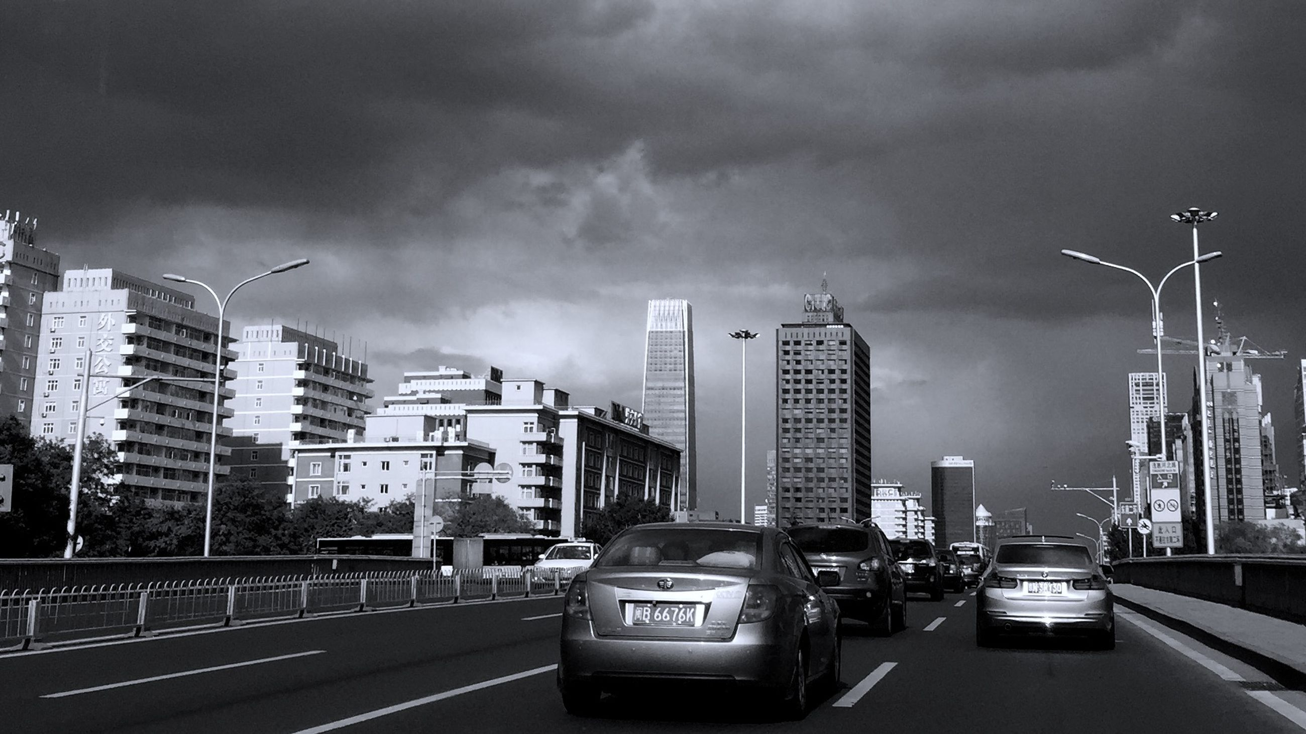 building exterior, architecture, city, built structure, transportation, sky, car, mode of transport, land vehicle, skyscraper, cloud - sky, street, modern, road, cloudy, city life, street light, tall - high, office building, on the move