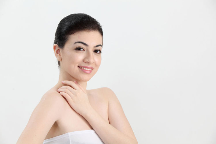Portrait of a young woman on the white background Asian  Beauty Skin Care Women Females Adult Real People White Background Studio Shot Black Hair Young Adult One Person Portrait Looking At Camera Beautiful Woman Young Women Indoors  Front View Lifestyles Headshot Smiling Copy Space Cut Out Healthy Spa Hairstyle Hair Bun
