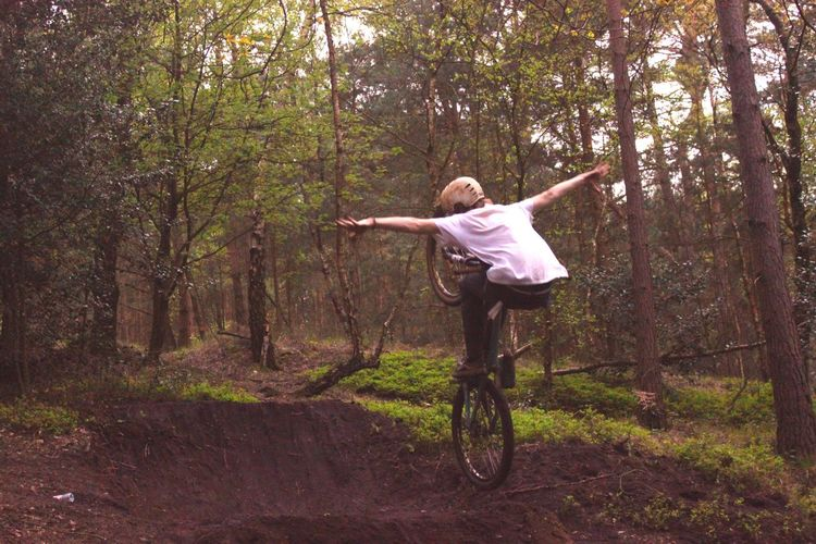 Full length rear view of teenage boy riding bicycle in forest