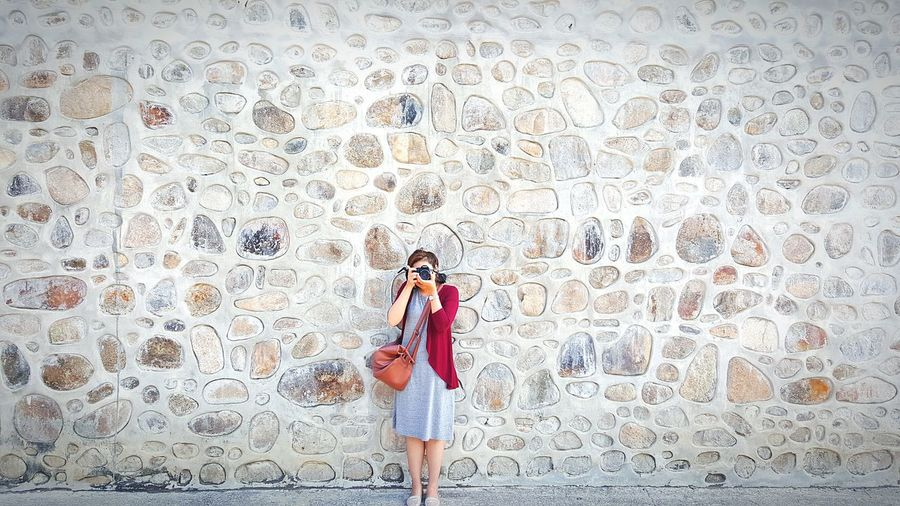 Woman photographing on footpath against wall