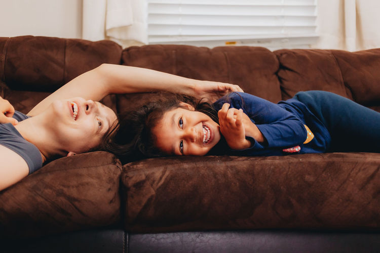 Smiling mother and daughter lying on sofa at home