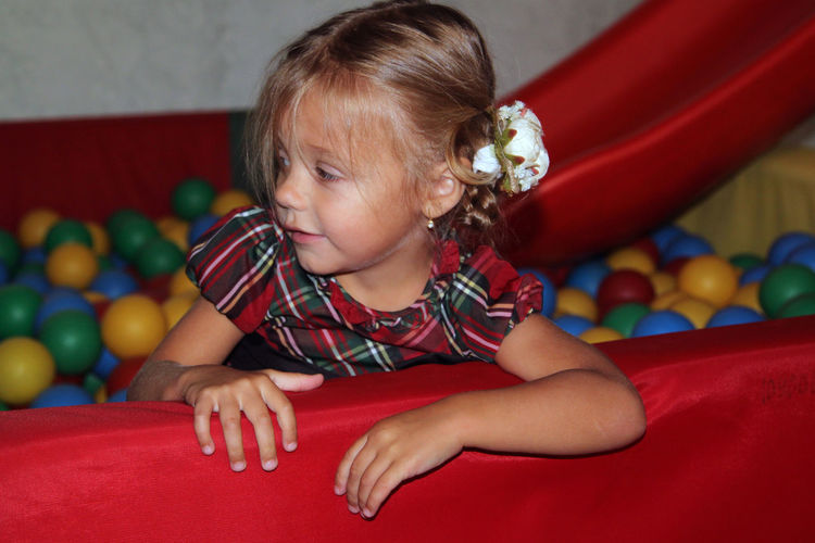 Cute girl looking away while sitting in ball pool