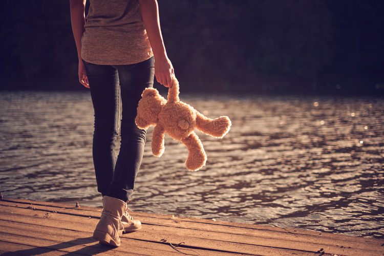 Low section of woman with teddy bear walking at lakeshore