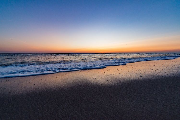 Sea Beach Scenics Sand Beauty In Nature Nature Water Sunset Shore Tranquil Scene Tranquility Horizon Over Water Clear Sky Wave No People Outdoors Sky Travel Destinations Blue Vacations