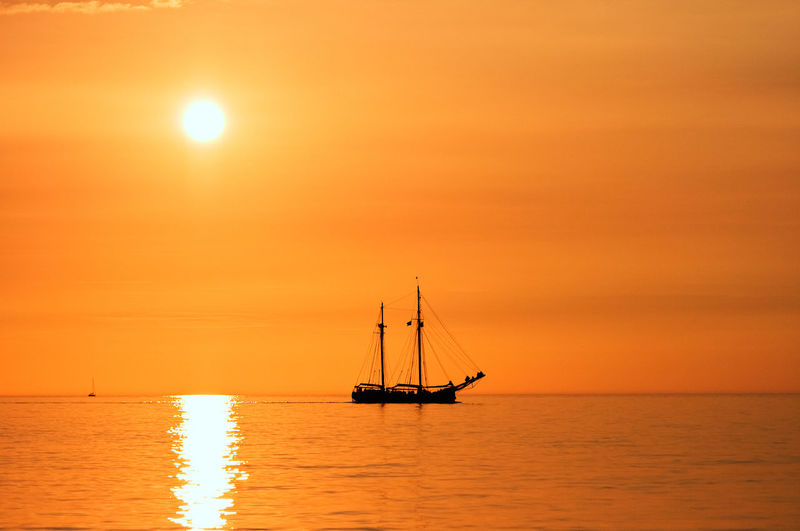 Silhouette sailboat sailing on sea against orange sky
