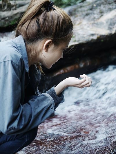 Side view of woman looking at water