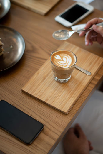 Coffee on Wooden Table in Cafe Drink Food And Drink Human Hand Human Body Part Refreshment Coffee - Drink Hand Coffee Mug Table Holding Cup Coffee Cup Wood - Material Indoors  One Person Adult Lifestyles High Angle View Latte Crockery Ijas Muhammed Photography
