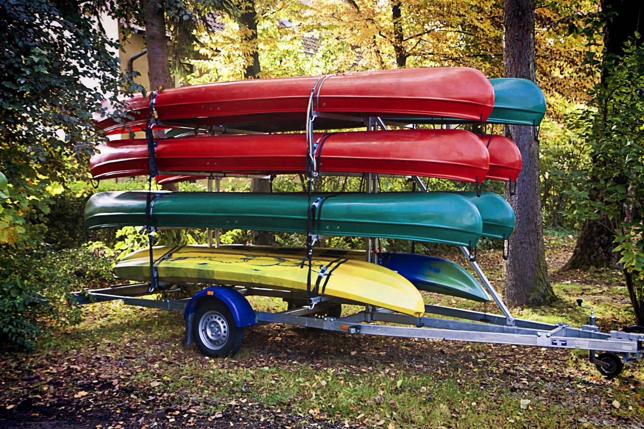 Upside Down Canoes On Vehicle Trailer Against Trees In Forest