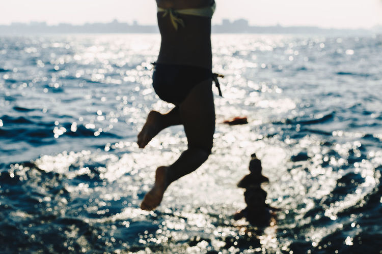 Low section of woman jumping on beach against sky