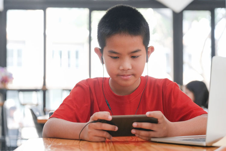 Boy using mobile phone while sitting on table