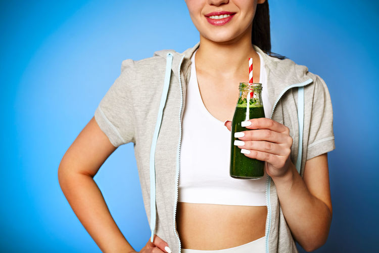 Midsection of woman holding while standing against blue background