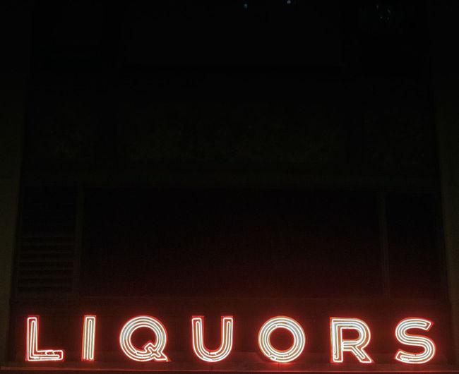 Illuminated Liquors Neon Sign Against Clear Sky At Night