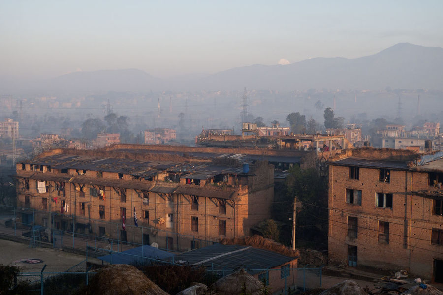 Hazy early morning sunlight over Bhaktapur in the Kathmandu Valley, Nepal, looking north Kathmandu Nepal Architecture Bhaktapur Building Exterior Built Structure City Cityscape Dawn First Light Hazy Morning High Angle View Mountain No People Outdoors Residential Building Sky