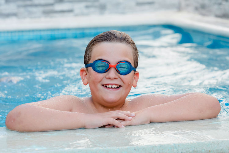 Portrait of smiling young man swimming in pool