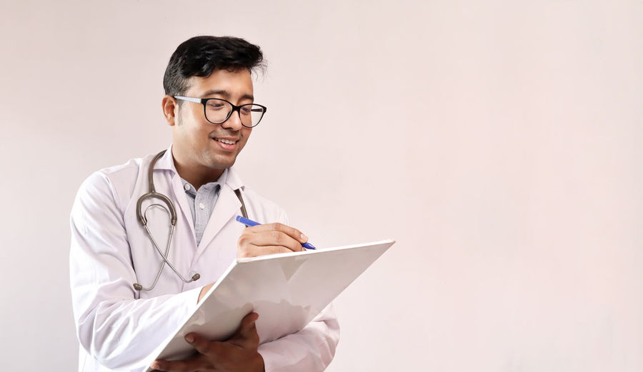 Doctor writing in paper against white background