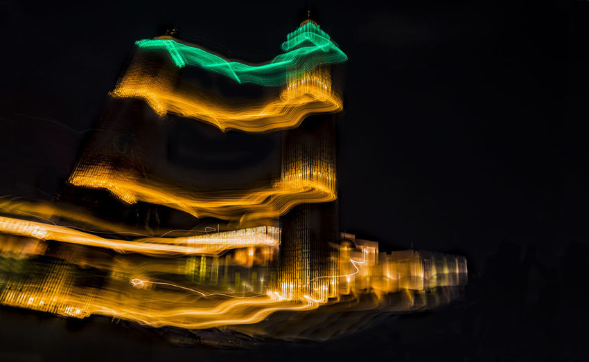 Illuminated built structure against sky at night
