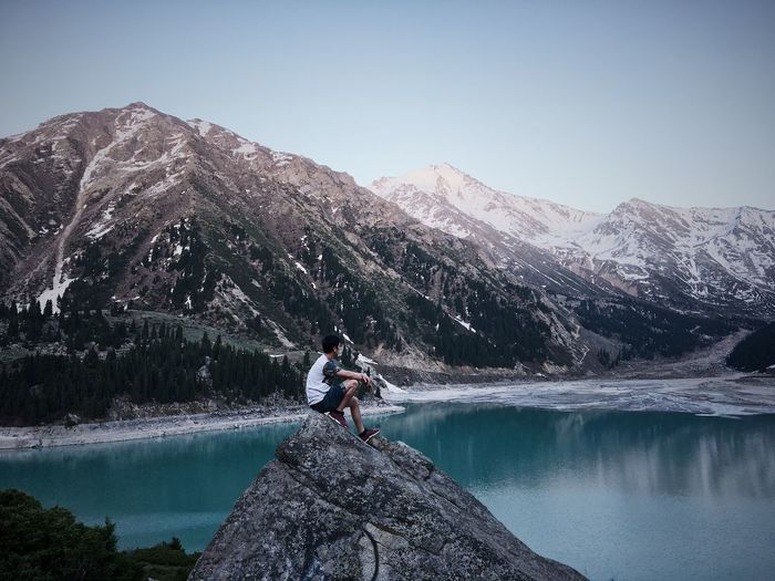 Side view of man sitting on rock by lake against mountains and sky