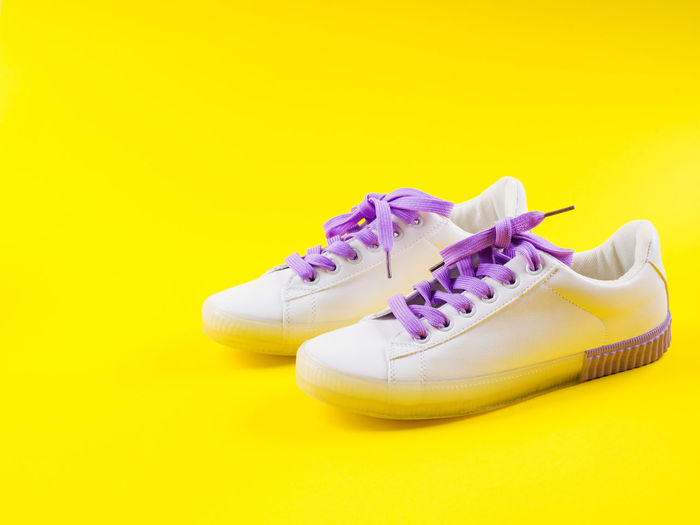 Close-up of shoes against yellow background