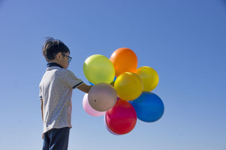 Boy holding multi colored balloons while standing against clear blue sky