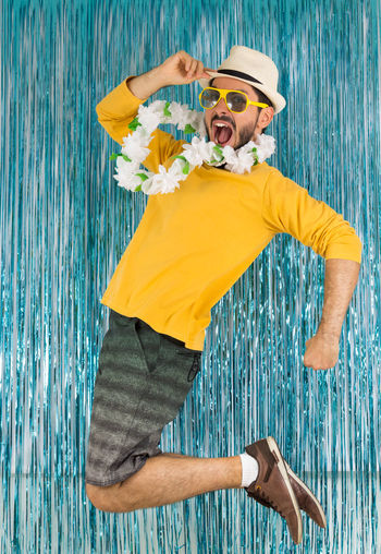 Portrait Of Happy Mid Adult Man Jumping Against Wall